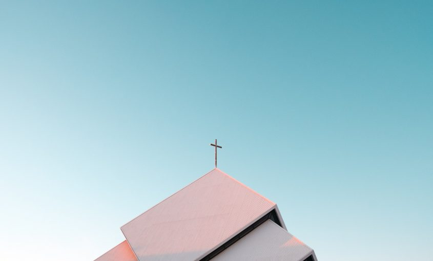 Top of a church building imposed on a white-blue gradient sky.
